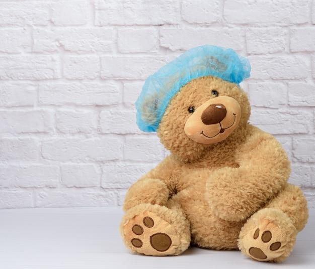 茶色のテディベアは、白いレンガの壁を背景に、医療用の使い捨ての青い帽子をかぶっています。流行中のウイルスからの保護アクセサリー