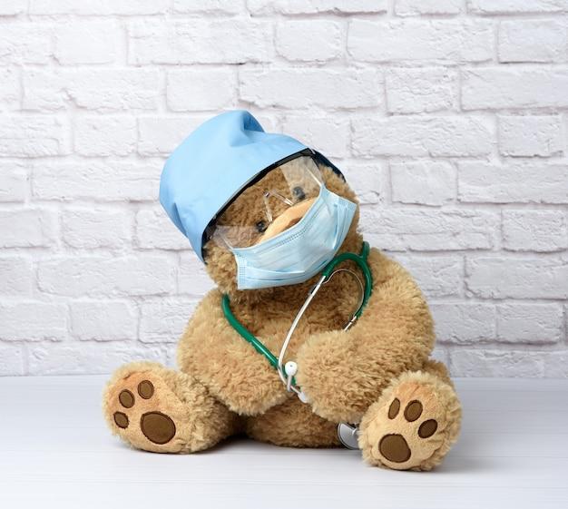 Коричневый плюшевый мишка сидит в защитных пластиковых очках, медицинской одноразовой маске и синей шапочке