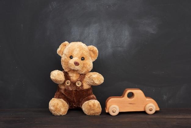 茶色のテディベアは茶色の木製のテーブルと木製の車に座っています。