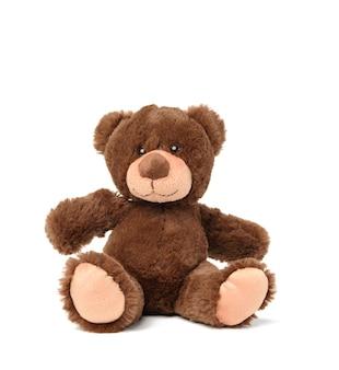 茶色のテディベアが白い表面に座っている、おもちゃ