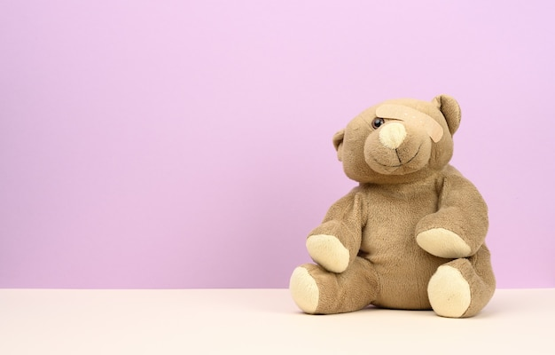 Brown teddy bear sits on a purple background, the eye is sealed with a medical brown plaster, copy space
