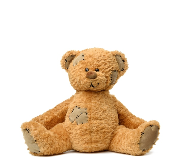 Brown teddy bear sits on a white background, toy with patches