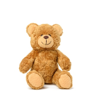 Brown teddy bear sits on a white surface, toy