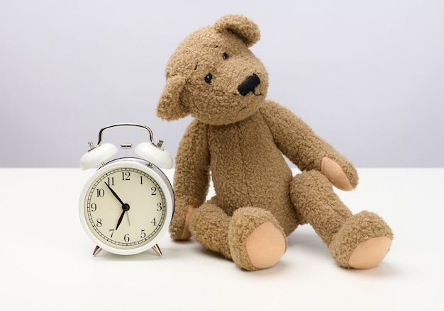 Brown teddy bear sits on a white table and a round alarm clock, at five minutes to seven in the morning