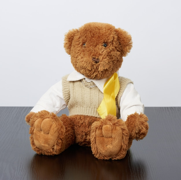 Brown teddy bear sits and a yellow silk ribbon