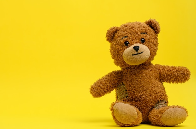 Brown teddy bear sits on a yellow wall, toy, copy space