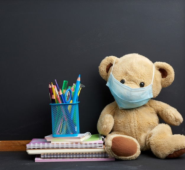 Brown teddy bear sitting in a disposable medical mask on a black chalkboard space