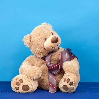 Brown teddy bear wearing a tie