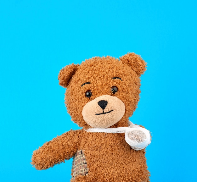 Brown teddy bear with a bandaged paw sitting on a blue background