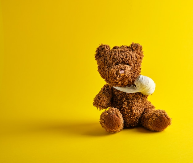 Brown teddy bear with a bandaged paw sitting