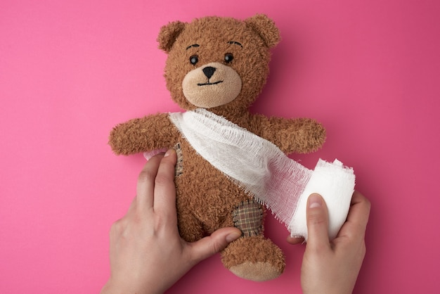 Brown teddy bear with bandaged torso with white gauze bandage on
