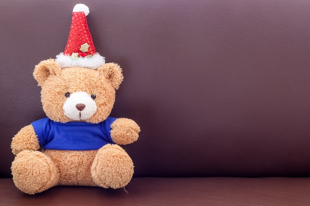 Brown teddy bear with blue shirt wearing christmas hat on the sofa