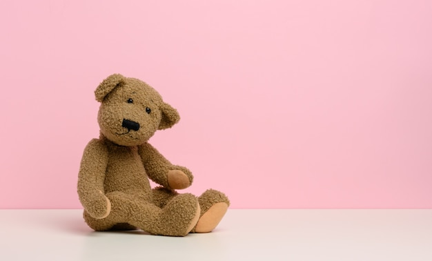 Brown teddy bear with patches sits on a white table, pink background, copy space