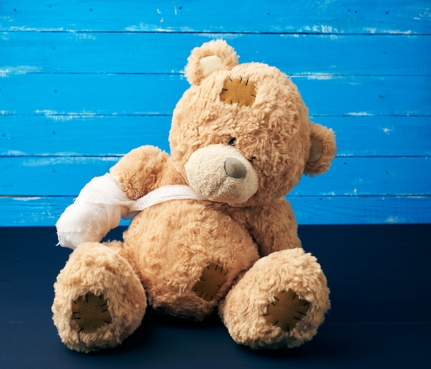 Brown teddy bear with rewound white bandage paw