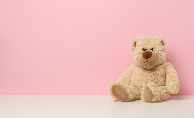 Brown teddy bear with a sad face sits on a white table, pink background, copy space