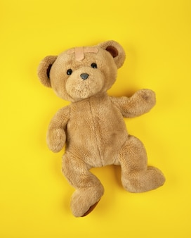 Brown teddy bear on yellow