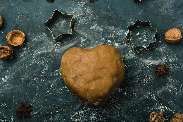 テーブルの上にハートの形をした生地を茶色にし、小麦粉をまぶしたほこり、上面図、濃い青色の背景。休日のコンテンツ