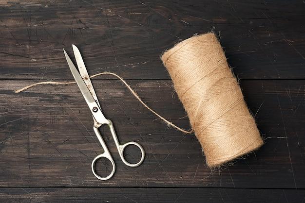 茶色の糸をスプールに巻き、ヴィンテージの金属はさみ