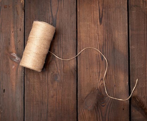 木製のテーブルのスプールにねじれた茶色の糸
