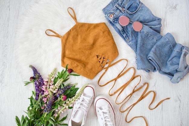 Коричневый топ с завязками, синие джинсы, белые кроссовки. букет полевых цветов. модная концепция