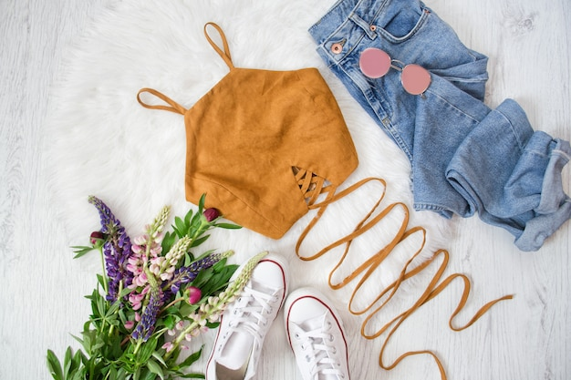 Brown top with ties, blue jeans, white sneakers. bouquet of wildflowers. fashionable concept