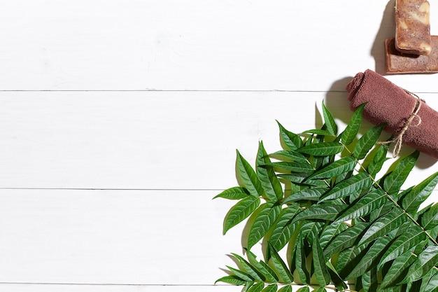흰색 나무 테이블에 갈색 수건과 천연 커피 비누, 위쪽 전망. 정물. 확대. 플랫 레이. 복사 공간