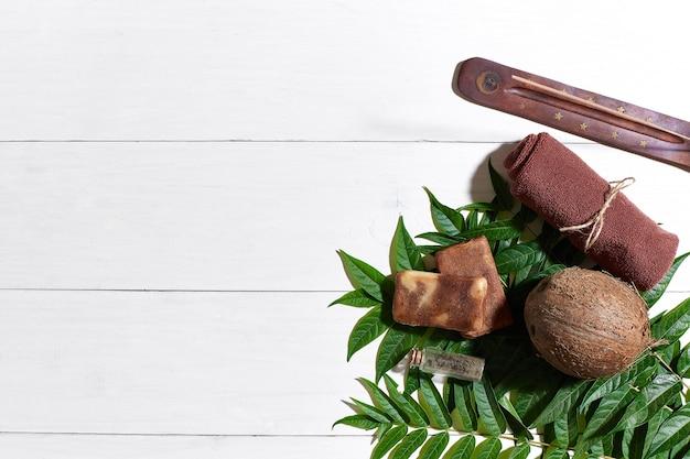 흰색 나무 테이블에 갈색 수건, 파란색 점토, 천연 커피 비누, 위쪽 전망. 정물. 확대. 플랫 레이. 복사 공간