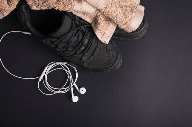 Brown towel on pair of shoes with white ear phone on black background