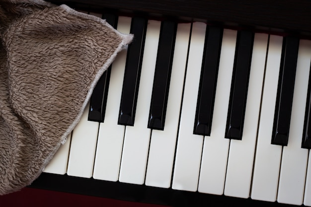 Brown towel on piano.