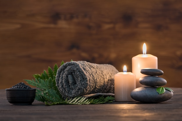 Brown towel  with candles and black hot stone on wooden background.