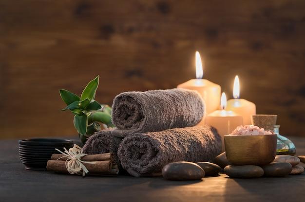 リラックスできるスパマッサージ用の竹とキャンドルが付いた茶色のタオル。