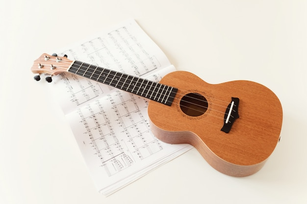 Brown ukulele guitar, sheet music. top view