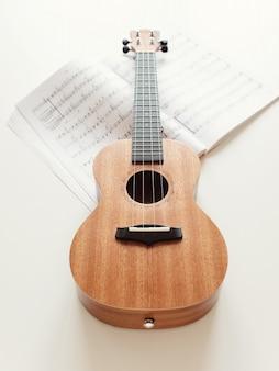Brown ukulele guitar, sheet music.