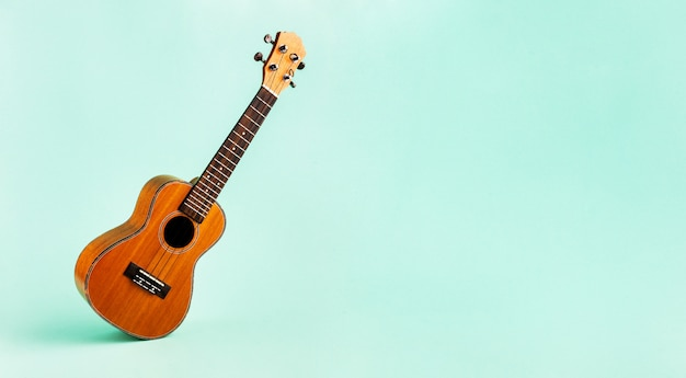 Brown ukulele isolated on abstract pastel turquoise background with wide copy space. creative concept.