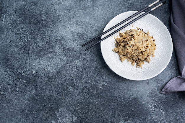 Brown and unpeeled rice on a plate with chopsticks.