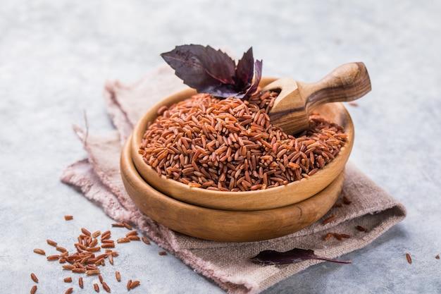 나무 그릇에 현미 현미. 긴 곡물 쌀 배경입니다.