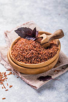 Brown unpolished rice in wooden bowl. long grain rice background.