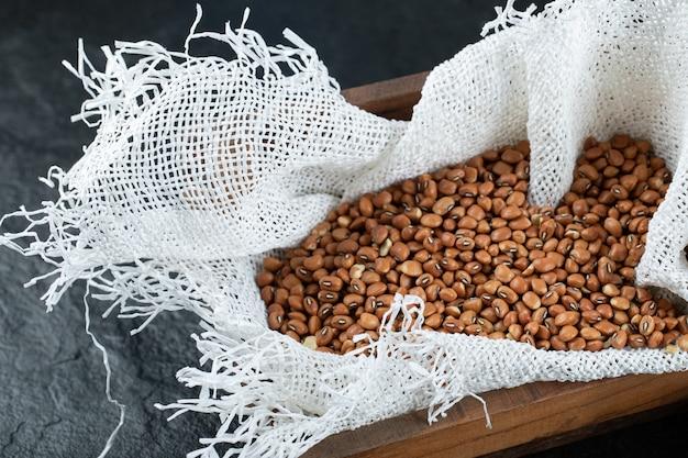 Fagioli nani non preparati marroni su un canestro di legno