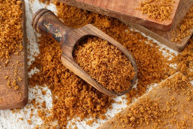 スプーンで茶色の精製されていないサトウキビの砂糖をクローズアップ