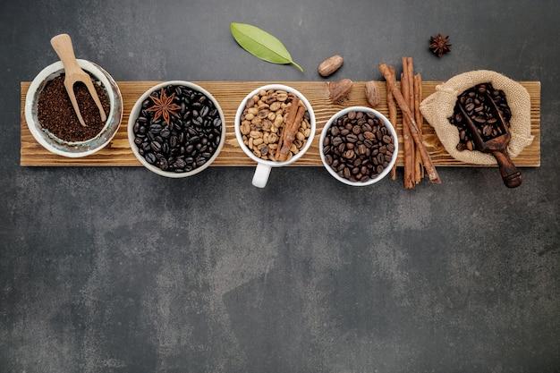 Коричневые необжаренные и темные обжаренные кофейные зерна в кофейной чашке с ложками на темном камне.