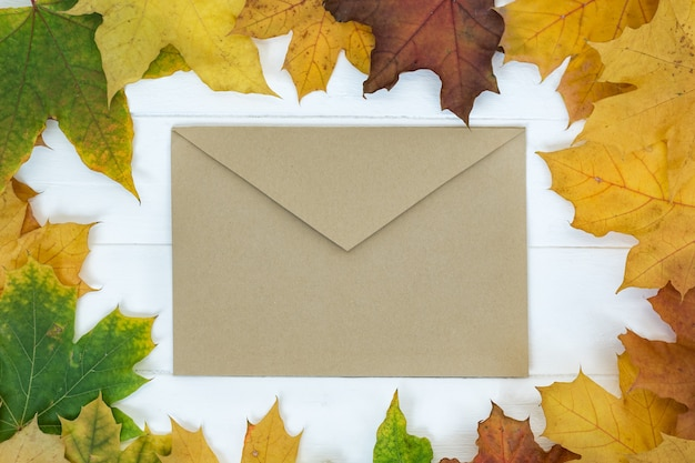 Brown vintage envelope on white surface in frame of autumn leaves
