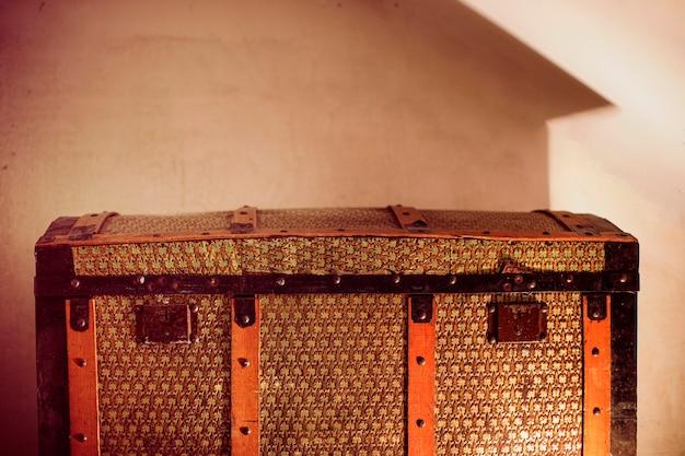 Коричневый старинный чемодан на стене