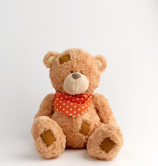 Brown vintage teddy bear with patches, white background