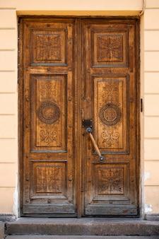 Коричневая старинная деревянная дверь с элегантной резьбой