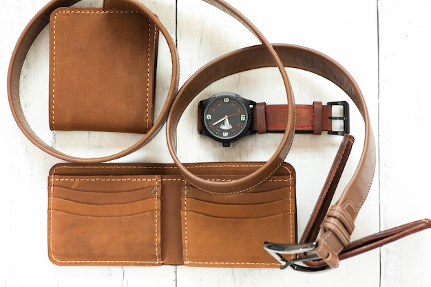 Brown wallet leather and belt accessory isolated. top view.