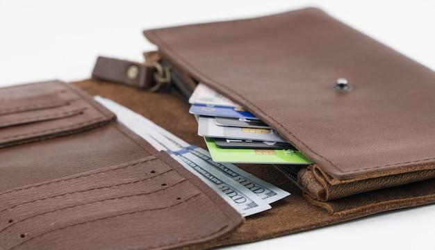 クレジットカードと白い背景の上の百ドル札が付いている茶色の財布。閉じる