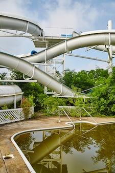 Коричневый бассейн с огромной водной горкой на заднем плане в заброшенном тематическом парке