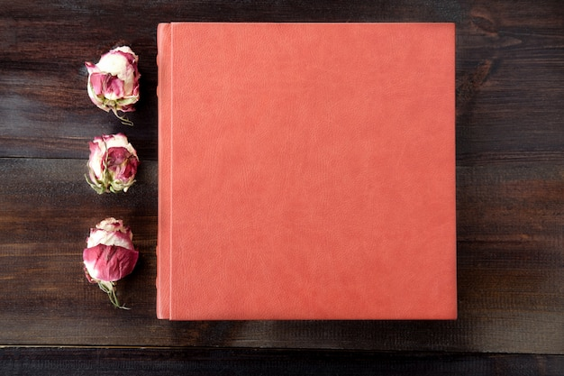Brown wedding album with rose flowers decoration on brown wooden background