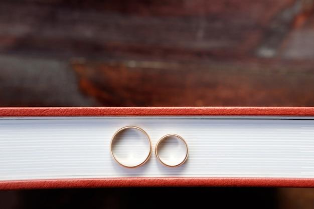 2つの結婚指輪と茶色の結婚式のアルバムは茶色の木製の背景にとどまる
