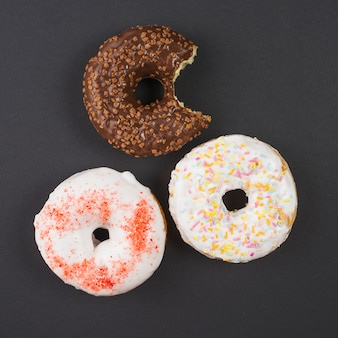 Brown and white bitten doughnuts with sprinkles on black background